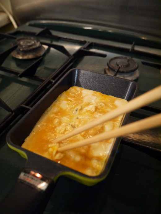 3. Pour 2/3 of the mixture into the pan and draw your chopsticks through the mix until the eggs are half cooked.