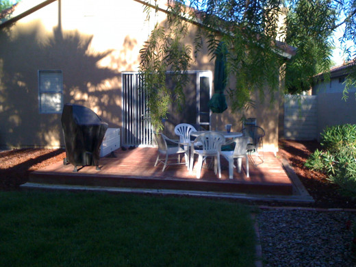 Just adding a few chairs, table, umbrella, and BBQ made all the difference on this backyard deck.