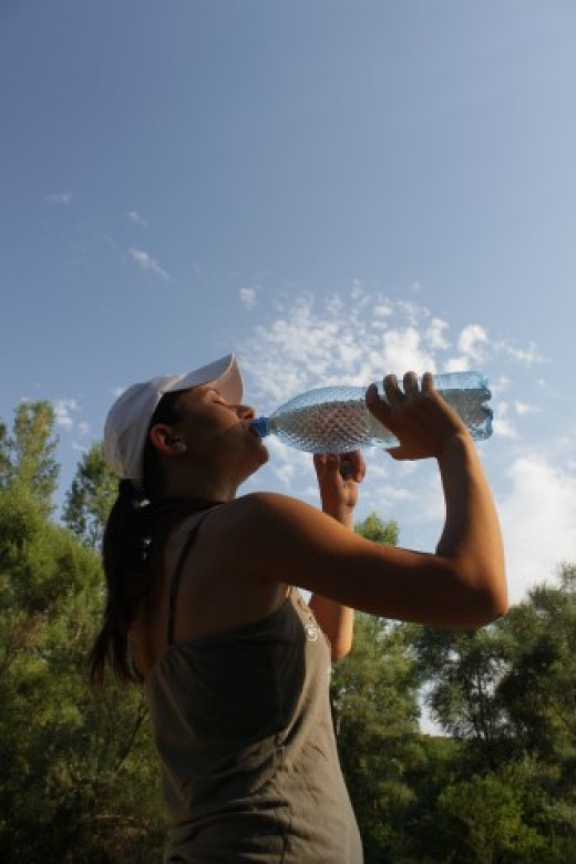 Thirsty Woman Drinking Water from a Bottle, Hot Summer and Blue Sky