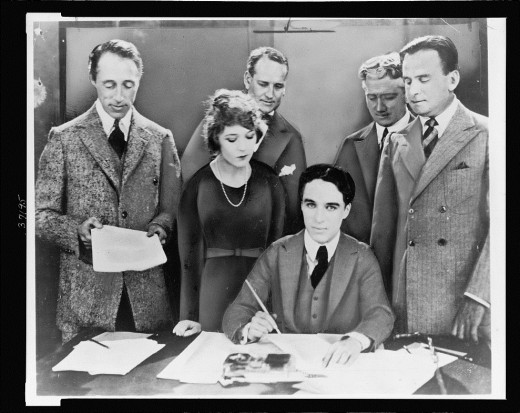 D.W. Griffith, Mary Pickford, Charlie Chaplin, and Douglas Fairbanks signing the contract that would establish United Artists. Circa 1919.