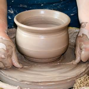 this shows a finished pot and the potter taking the taut cutting wire and sliding it under the pot as close to the wheel head as possible