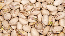 Mature dried pistachios with open shells with some natural freckles on their surfaces