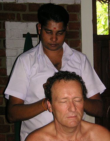 An Ayurveda practitioner applying oils using head massage.