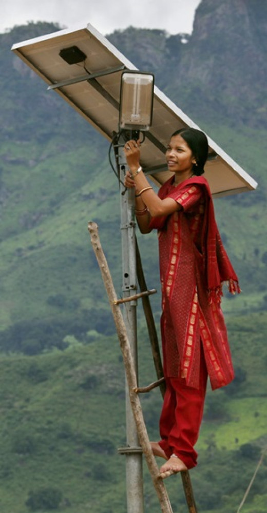 A village girl installing a solar street light!