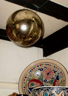 A traditional witch ball hangs from the rafters.