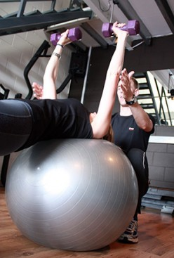 Another good example here, this time spotting a client on the fitball doing a dumbbell chest press.