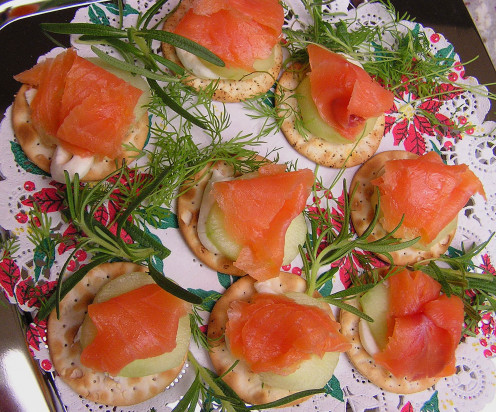 Smoked salmon canapes are simple to put together.  Just choose a cracker of any type ; add a dollop of cream cheese topped with slice of cucumber.  Top it off with a thin slice of smoked salmon and you are done. Yum!