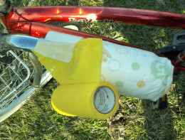 Set the vet wrap at an angle on the handlebar to prepare for wrapping the diaper.