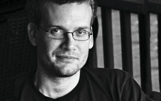 A faux-artistic black-and-white photo of a smirking John Green.