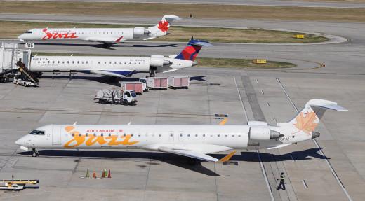 Bombardier CRJ aircraft near airport terminal sky bridge.