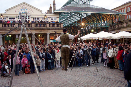 A tight-rope walker entertains a crowd in Covent Garden.