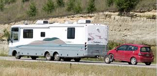 A motorhome towing a vehicle using a Tow Dolly, usually used to tow front-wheel drive vehicles.