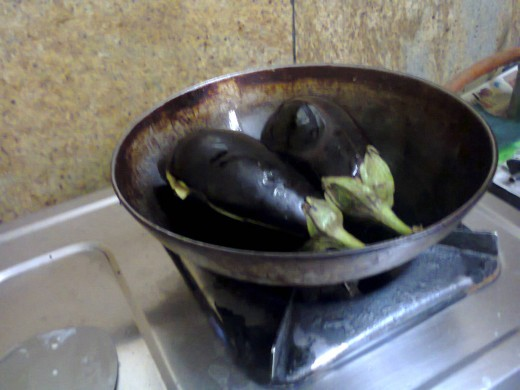 cut brinjals placed into deep fry pan after dropping some oil in the pan.