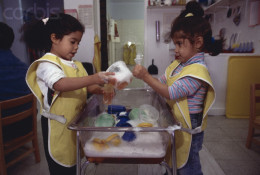 The two Day Care students learn the art of pouring cake batter