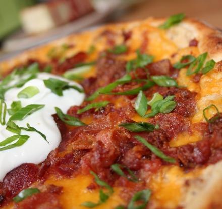 Pizza Skins - garlic mashed potatoes, cheddar cheese, bacon and scallions, baked on a pizza dough and then topped with sour cream.