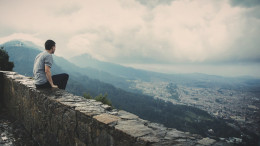 A man sitting on a wall overlooking a city.