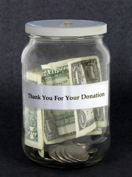 donation jar with green dollar bin and the words thank you for your donation typed on the jar