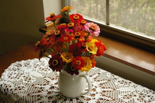 Spring flower bouquet of Zinnias on the windowsill.