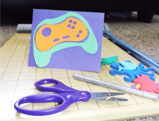 """Cut the """"Controller Pad"""" template from foam. Use the craft knife to cut out small pieces like the larger circle and the two small oblong pieces. Punch the small circles out with the hole puncher. Glue it inside the open space in the """"Base"""" layer of f"""