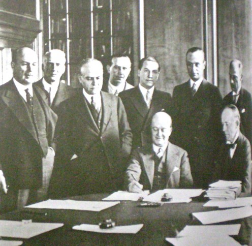 "Vice President Roca signing the Roca-Runciman Treaty in 1933 with Sir Walter Runciman (seated, right) Source: ""Historia Argentina"". Autor: Diego Abad de Santillán. TEA, Tipográfica Editora Argentina. 1971, Buenos Aires, Argentina"