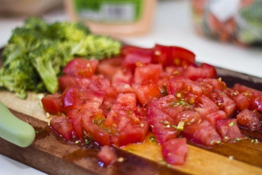 A ripe tomato, chopped up and ready to go, along with some chopped broccoli.