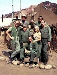 M*A*S*H core cast, Mike Farrell, Harry Morgan, Loretta Switt, Alan Alda, sitting, William Christopher, Jamie Farrar, and David Ogden Steirs back row.