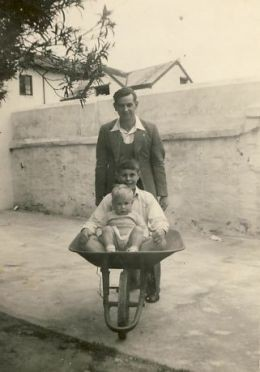 Dad pushing me (in front) and Chris in a wheelbarrow at the back of Aunt Queenie's house