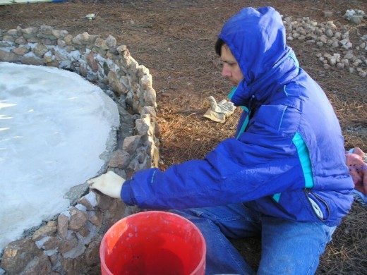 I gradually built up a rock facing by hand, using thick gobs of premixed mortar. Cement products are very corrosive to the skin. Note the surgical gloves I wore while putting the rocks in place.