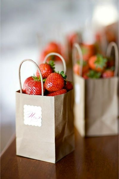 Strawberries in small paper bags as table numbers