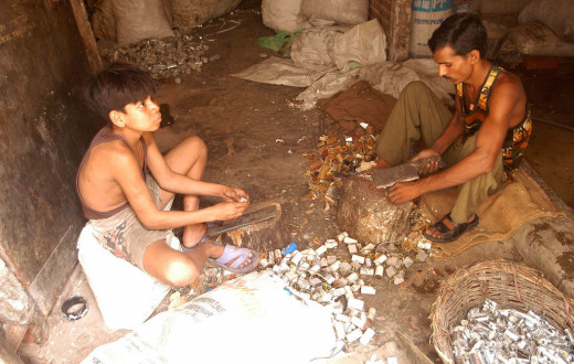Workers use cleavers for extracting metal parts from used capacitors. Delhi