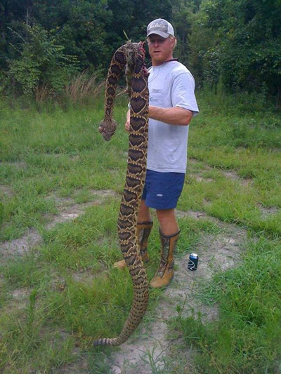 LOOK at this! The man stands six foot, two inches tall. Now look at the length of the rattler.