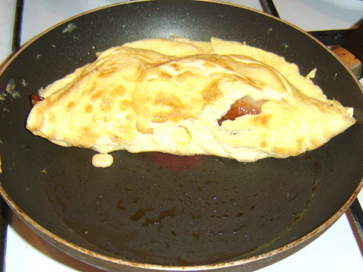 Duck egg omelette is folded over sausages and bacon