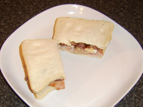 Hard boiled eggs are sliced and made in to a sandwich with sausages and back bacon