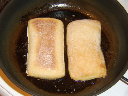 Cut sides of ciabatta roll are lightly toasted in frying oil