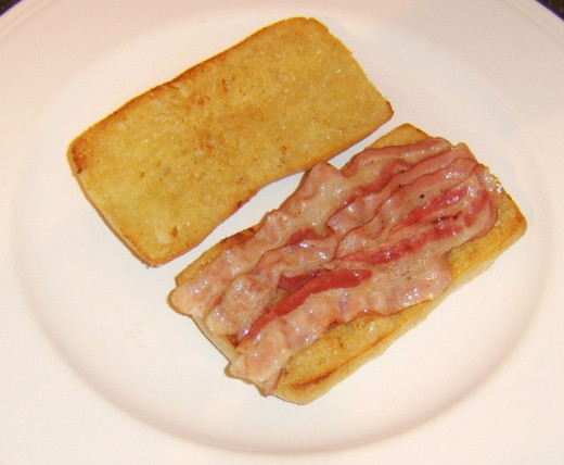 Pancetta is laid on bottom half of ciabatta roll