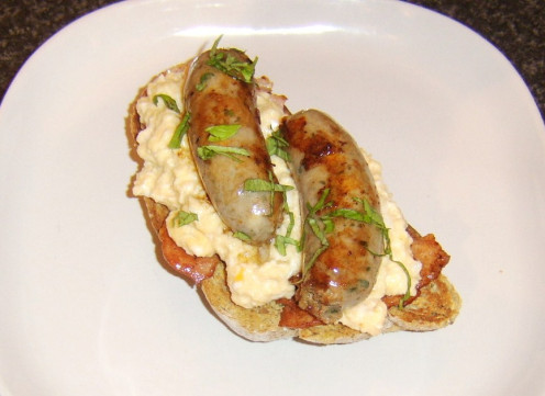 Bacon, scrambled egg and sausage arranged on toast and garnished with fresh basil