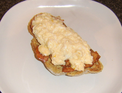 Scrambled egg is spooned on top of bacon