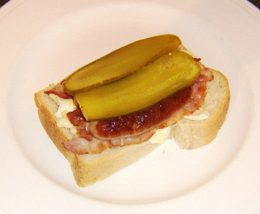 Pickles are the final sandwich additions before it is topped with a second slice of bread