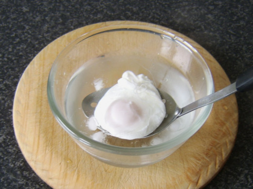 Poached egg is dipped briefly in iced water to stop it cooking