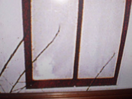 Bottom left window corner spirit of Boyd or Paul Moore captured by a paranormal team at the Villisca Ax Murder House, and re-photographed.