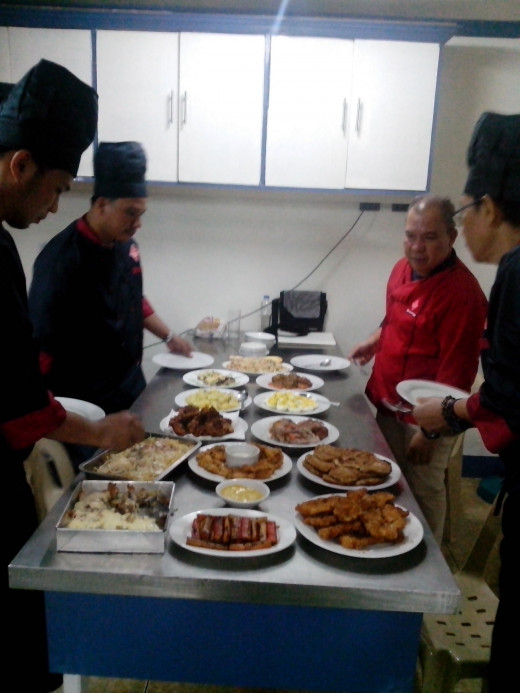 Our chef-instructor/assessor Noel M. Itable (in red uniform) inspecting our food plating Photo Source: Ireno A. Alcala