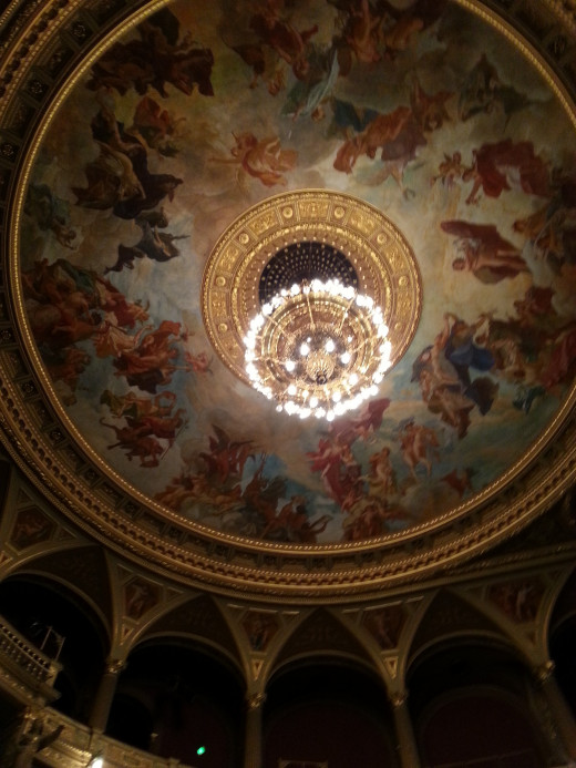 The view of the chandelier and frescoes above the main gallery of the Hungarian State Opera House.