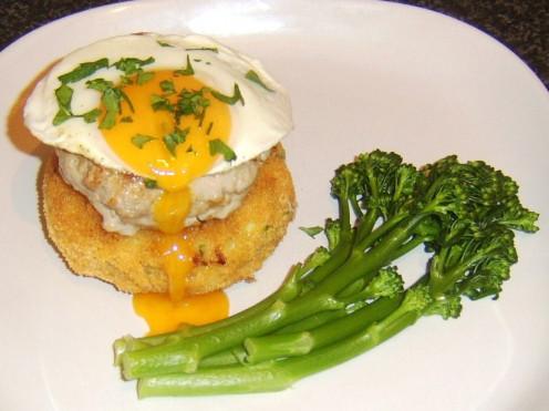 Succulent pork burger on a breaded potato cake with fried egg and broccoli