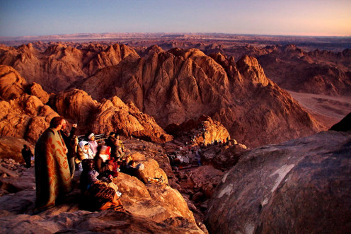 Beautiful shot of colored canyons of Sinai mountain and the early birds camping at the right spot for viewing the sun emerging out from mountains