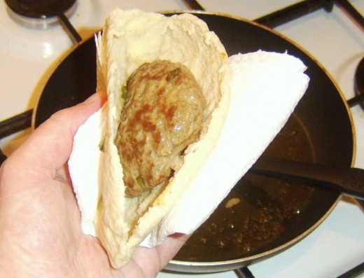 Lamb burger is placed in cut pitta bread