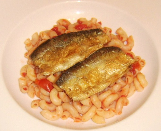 Cooked herring fillets are laid on top of the macaroni