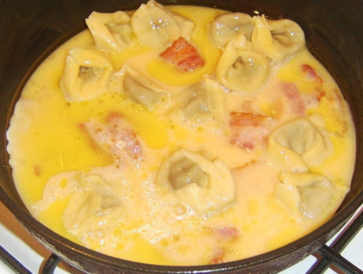 Starting to fry bacon and mushroom tortelloni frittata