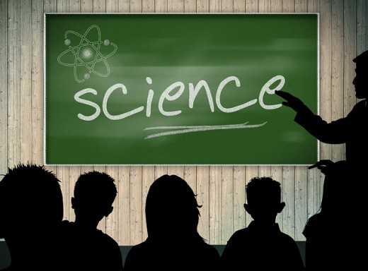 "a balck board with silohuettes of people looking at the word written in white chaulk - ""science"""