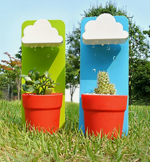 These rain cloud watering devices water the plants from artificial raindrops falling from the cloud reservoirs above the plants