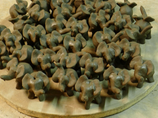 Tiny elephants come to life from plain clay.